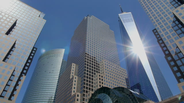 tu pan camera captures one world trade center and skyscrapers at world financial center.the sun illuminate one world trade center. - tilt up stock videos & royalty-free footage
