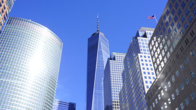 vídeos de stock, filmes e b-roll de camera captures one world trade center and the other lower manhattan buildings in new york city. an american flag is shaking by winds on the top of building. - torre da liberdade nova iorque