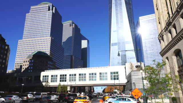 Camera captures One World Trade Center and World Finance Center and other structures in Lower Manhattan district at New York. West Street traffic goes through under the elevated passageway.