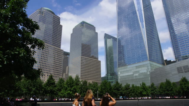 tu camera captures one world trade center and world financial center buildings at 911 memorial. can be seen visitors around the south pool. - drei personen stock-videos und b-roll-filmmaterial