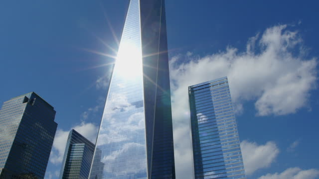 TU Camera captures One World Trade Center which is illuminated by the sun at National September 11 Memorial.Clouds is moving slowly behind tower.