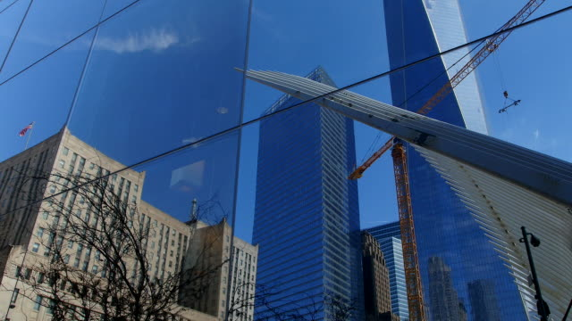 TD Camera captures One World Trade Center which is reflected to building windows.An American flag is waving by wind.Construction crane can be seen in middle.