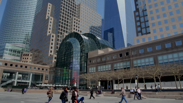 TU Camera captures people and One World Trade Center and skyscrapers at World Financial Center.