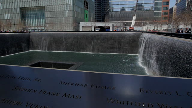 TU Camera captures people and One World Trade Center which is illuminated by the sun at National September 11 Memorial.