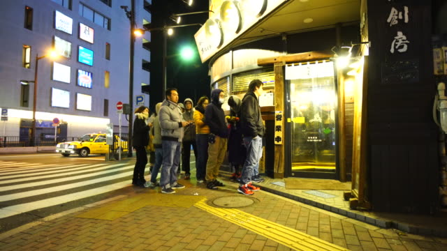 camera captures people are waiting to eat ramen noodle at the mutekiya after the midnight in ikebukuro toshima-ku tokyo. - people in a line stock videos & royalty-free footage