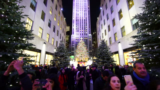 vídeos y material grabado en eventos de stock de camera captures people, christmas decorations and christmas tree at rockefeller center at night in christmas holidays season 2016 new york. people watch the 2016 saks fifth avenue holiday light show and take photo from rockefeller center. - centro rockefeller
