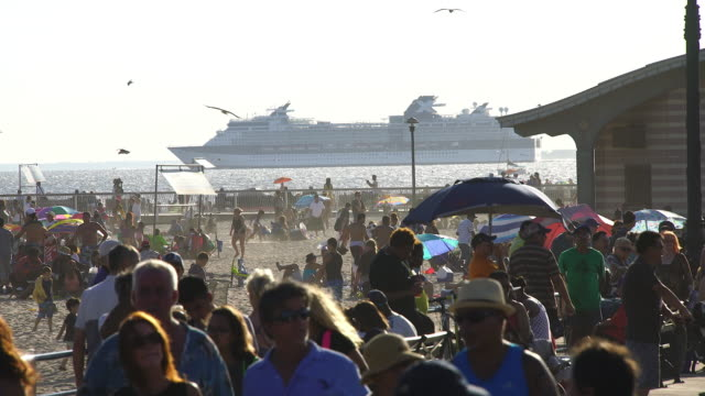 Camera captures people on the beach and crowd who walk down the Coney Island Boardwalk. One large cruise ship runs on the sea behind beach.