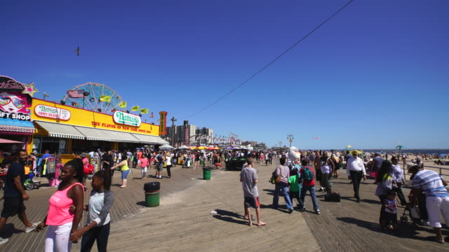 PAN Camera captures people on the beach and walk down the boardwalk at Coney Island Brooklyn. There are many shops and restaurants beside the boardwalk.