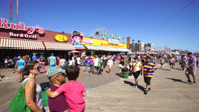 pan camera captures people on the beach and walk down the boardwalk at coney island brooklyn. there are many shops and restaurants beside the boardwalk. - coney island stock-videos und b-roll-filmmaterial