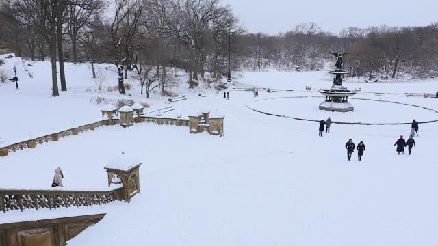 vídeos de stock e filmes b-roll de pan camera captures people walking at snowy bethesda terrace. - fonte bethesda