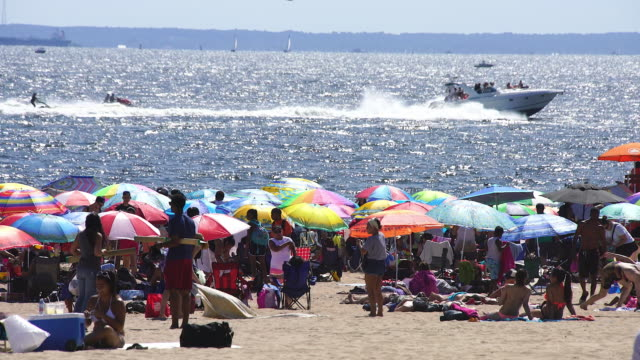 Camera captures people who are bathing in the sun at crowded Coney Island Beach. There are many colorful beach parasols on the beach. Boats run on shiny sea that illuminated by afternoon sunlight.