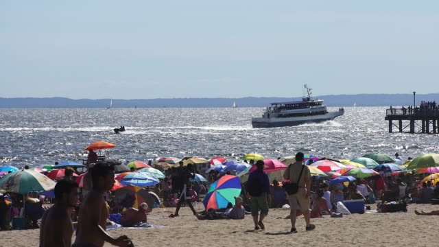 pan camera captures people who are bathing in the sun at crowded shiny coney island beach. there are many colorful beach parasols on the beach. boats runs on shiny sea that illuminated by afternoon sunlight. - coney island brooklyn stock videos & royalty-free footage