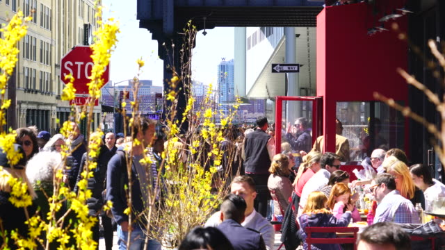 camera captures people, who are eating lunch at sidewalk tables of restaurant on gansevoort street at meatpacking district in manhattan. - brunch stock videos and b-roll footage