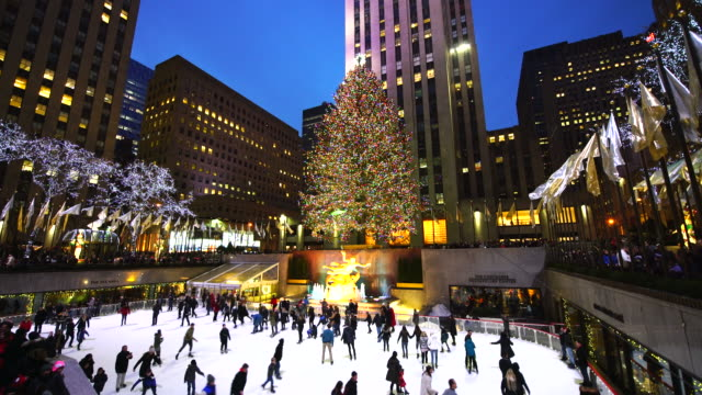 camera captures people, who are enjoying ice-skating at the rink at rockefeller center at night in christmas holidays season 2016 new york. - rockefeller center video stock e b–roll