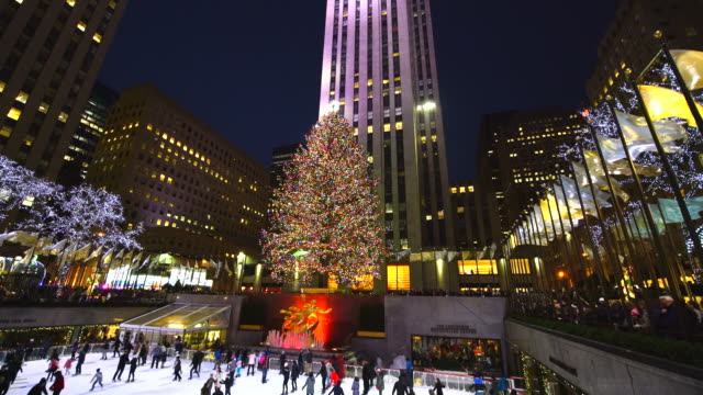 camera captures people, who are enjoying ice-skating at the rink at rockefeller center at night in christmas holidays season 2016 new york. - rockefeller centre stock videos & royalty-free footage
