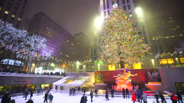camera captures people, who are enjoying ice-skating during the snow night at the rink at rockefeller center midtown manhattan. - rockefeller center christmas tree stock videos & royalty-free footage