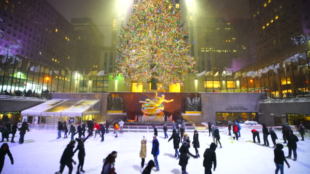 camera captures people, who are enjoying ice-skating during the snow night at the rink at rockefeller center midtown manhattan. - rockefeller center video stock e b–roll