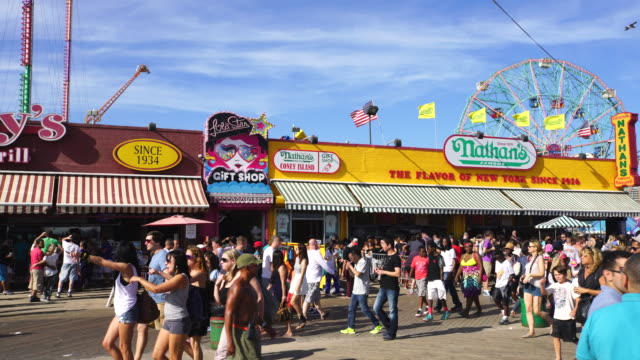 PAN Camera captures people who walk down the boardwalk at Coney Island Brooklyn. There are many shops and restaurants behind crowd.