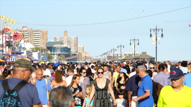 PAN Camera captures people who walk down the boardwalk at Coney Island Brooklyn. There are many shops and restaurants beside boardwalk.
