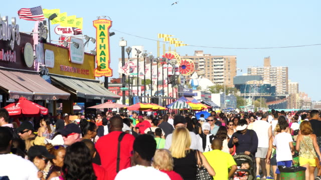 tl pan camera captures people who walk down the boardwalk at coney island brooklyn. there are many shops and restaurants beside boardwalk. - coney island stock-videos und b-roll-filmmaterial