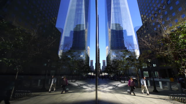 camera captures people who walk on the street and one world trade center reflected to building window. - 歩道点の映像素材/bロール