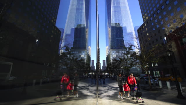 Camera captures people who walk on the street and One World Trade Center reflected to building window.