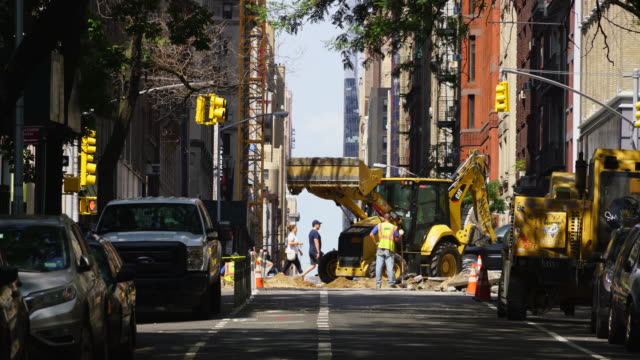 camera captures road construction site at midtown manhattan new york city - construction vehicle stock videos and b-roll footage
