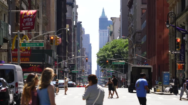 camera captures rows of buildings along the broadway at central village district manhattan new york city. people cross the street and, there are no running cars for street closure - pedestrian stock videos & royalty-free footage