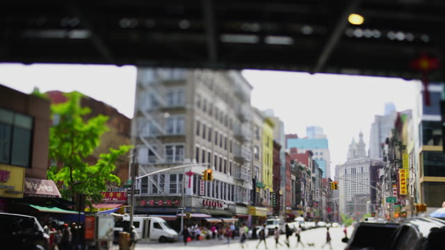 vídeos y material grabado en eventos de stock de camera captures rows of chinatown buildings along the street from under the manhattan bridge at new york city ny usa on may. 22 2019. - tilt shift