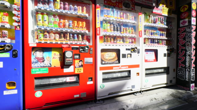 camera captures rows of drink vending machines. adult software shop signboard can be seen in the right. - 機械類点の映像素材/bロール