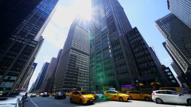 Camera captures Sixth Avenue Traffic among the Midtown Manhattan skyscrapers at New York City. The sun shines over the skyscrapers.
