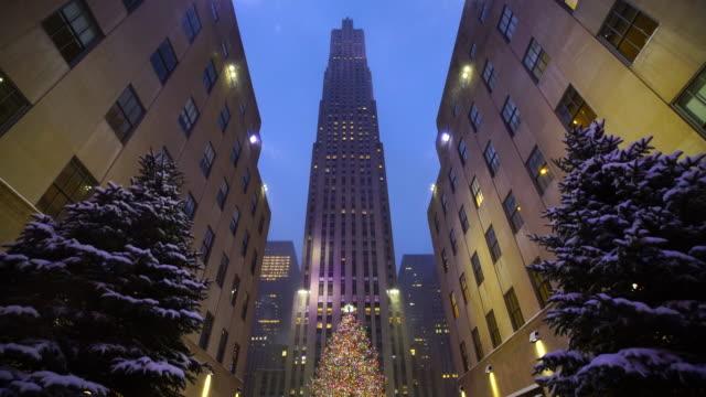 vídeos de stock, filmes e b-roll de camera captures snowy christmas decorations and christmas tree at rockefeller center in christmas holidays season 2016 new york at dusk. - centro rockefeller