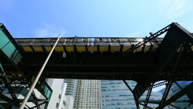 Camera captures subway which run on the elevated railroad in front of new highrise residences.