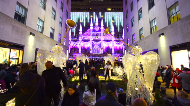 camera captures the complete 2016 saks fifth avenue holiday light show at night from rockefeller center in midtown manhattan. people watch the 2016 saks fifth avenue holiday light show and take photo from rockefeller center. - ウィンターコート点の映像素材/bロール