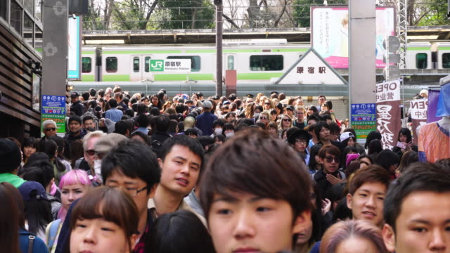 Camera captures the crowd in Takeshita Dori. Harajuku Station and Yamanote Line can be seen behind crowd.