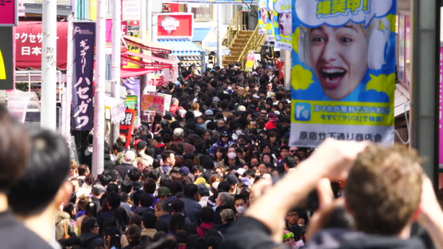 camera captures the crowd in takeshita dori. there are many fashion boutiques, cafes and restaurants along both side of the street. - chaos stock videos & royalty-free footage