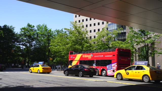 Camera captures the Double Decker Tour Bus and taxis at front of fresh green trees at Lower Manhattan New York.