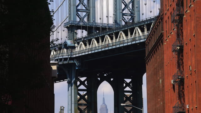 TU Camera captures the Empire State Building through the Manhattan Bridge Bridge pier at Brooklyn. Trucks run on the bridge.