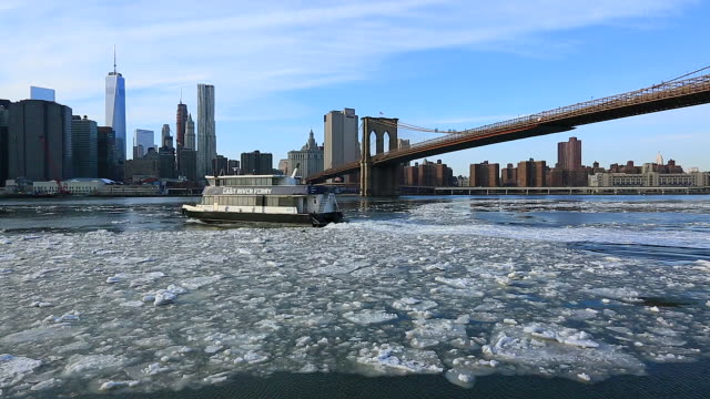 TL PAN Camera captures the Ferry boat crossing the drifting ice under the Brooklyn Bridge at East River.Downtown Manhattan skyscrapers can be seen behind.