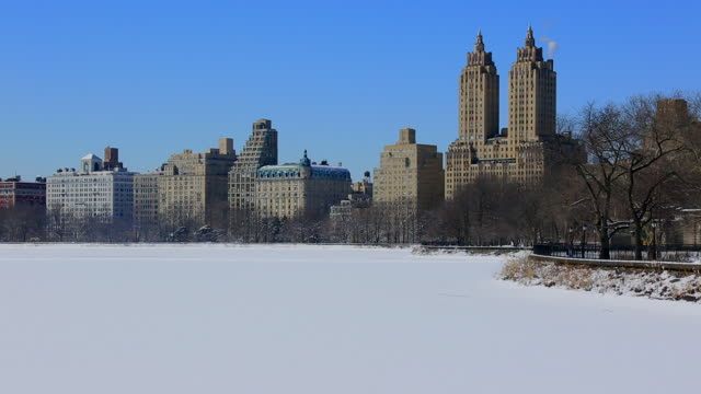 pan camera captures the frozen reservoir and central park west residences.reservoir is completely frozen for cold temperature which is covered by snow. - central park reservoir stock videos and b-roll footage