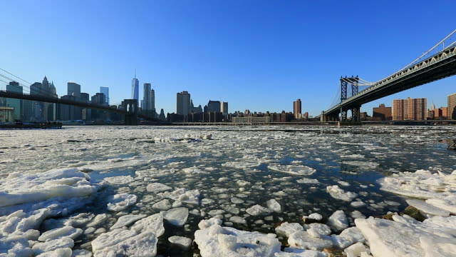 pan camera captures the icy east river which wrapped up by drift ice between brooklyn bridge and manhattan bridge.downtown manhattan skyscrapers and brooklyn bridge can be seen behind icy east river.manhattan bridge and residence can be seen. - brooklyn bridge stock videos & royalty-free footage