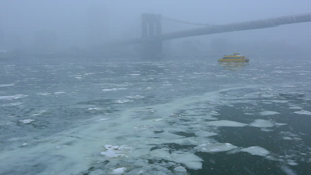 Camera captures the moving drift ice which covered East River during the snowing.Ferry boat runs through under the hazy Brooklyn Bridge by snow.