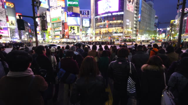 Camera captures the pedestrian and night cityscape at Shibuya Intersection on Sunday evening at dusk.