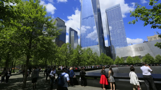 TL TU Camera captures the people at Memorial South Pool and Freedom Tower which are surrounded by fresh green trees at 911 Memorial Park.Clouds is moving at the sky.World Financial Center and other skyscrapers can be seen behind.