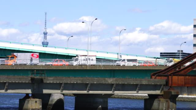 Camera captures the traffic of the Harumibashi Bridge, which is over the Harumi Canal and connects Harumi, Chuo ward to Toyosu, Koto ward Tokyo. Tokyo Sky Tree can be seen behind the Harumibashi Bridge.