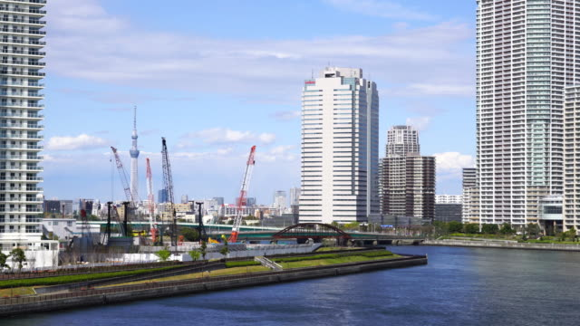 Camera captures Tokyo Sky Tree and huge cranes, which stand among the High-rise Condominium Tower Mansions. Harumi Canal. Harumi ward is at left side and Toyosu ward is at the right side.
