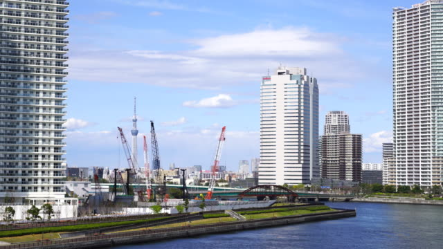 camera captures tokyo sky tree and huge cranes, which stand among the high-rise condominium tower mansions. harumi canal. harumi ward is at left side and toyosu ward is at the right side. - 運河点の映像素材/bロール