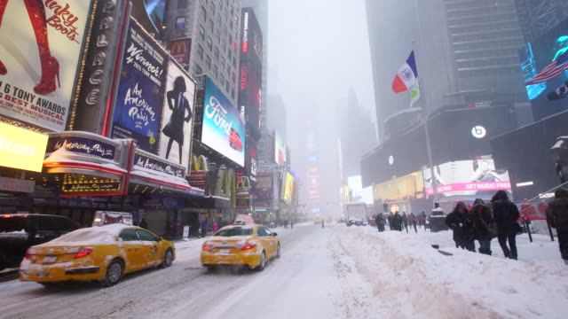 Camera captures traffic and neon billboard at Times Square during the serious winter snowstorm Jonas.