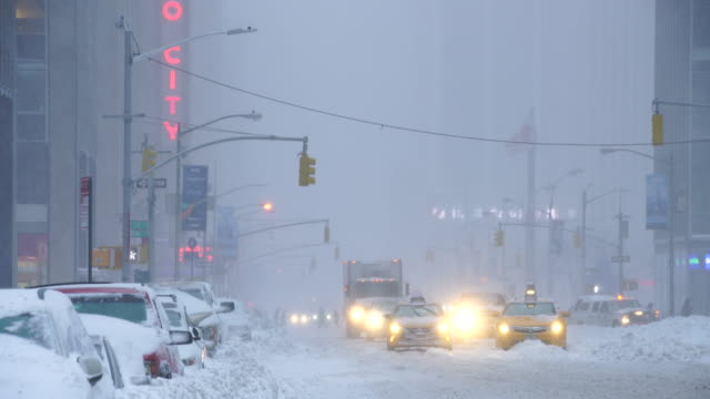 camera captures traffic of 6th avenue during the serious winter snowstorm jonas.road and cars were covered by snow and visibility is bad for snowing. - radio city music hall stock videos & royalty-free footage