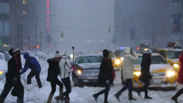 vídeos de stock e filmes b-roll de camera captures traffic of 6th avenue during the serious winter snowstorm jonas.road and cars were covered by snow and visibility is bad for snowing.pedestrians are crossing the avenue and a man is shoveling snow. - pá para neve